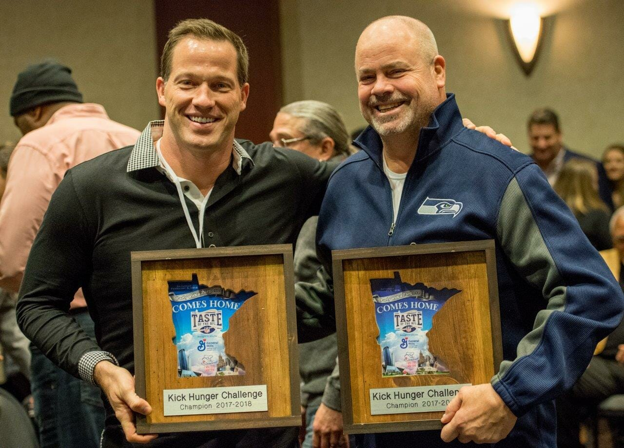 Seahawk Craig Terrill and Chef John Howie, head of Seattle's Kick Hunger Challenge team, hold up the awards for winning.